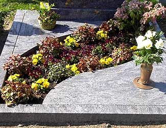 Blumen auf einem Grab zwischen Mamorplatten